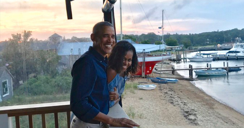 Barack and Michelle Obama laughing on a porch near some boats and water